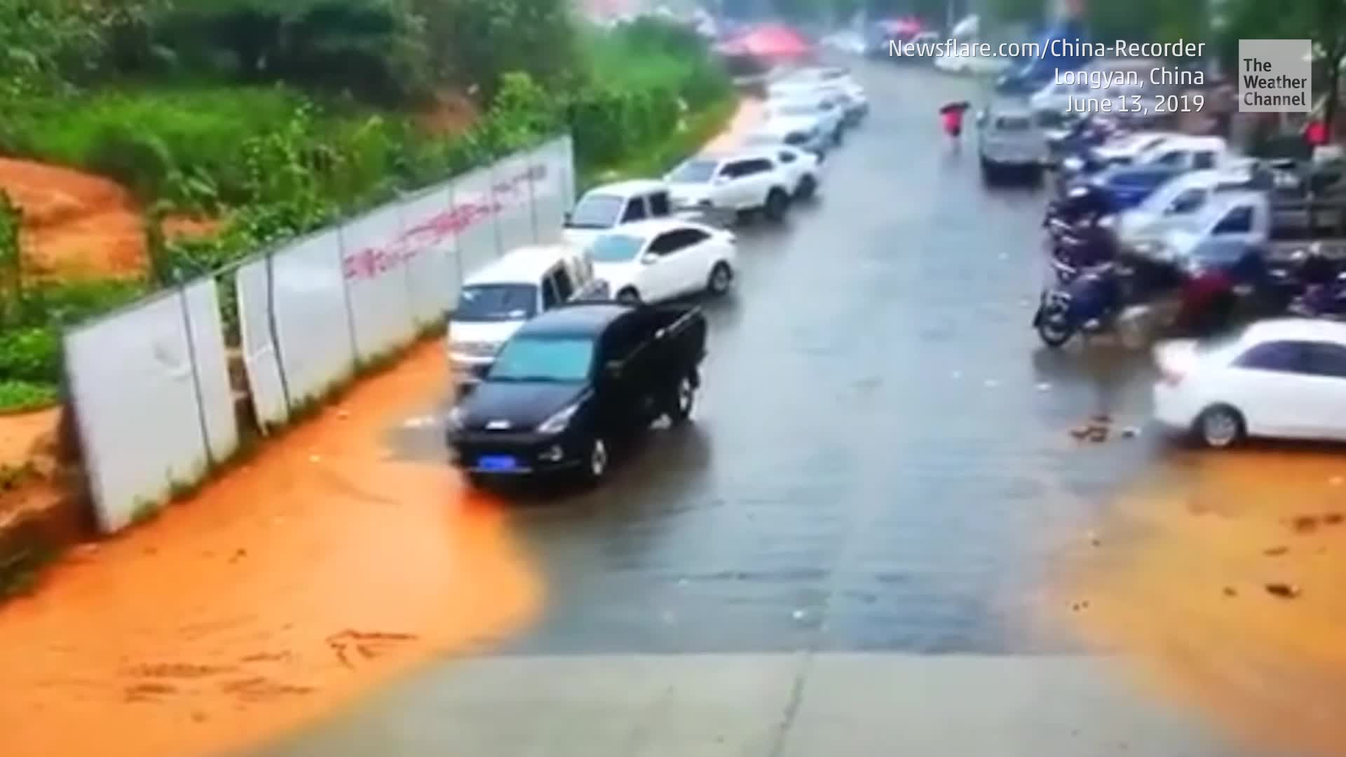 Heavy rain caused a hillside to crumble, covering a street full of parked cars.