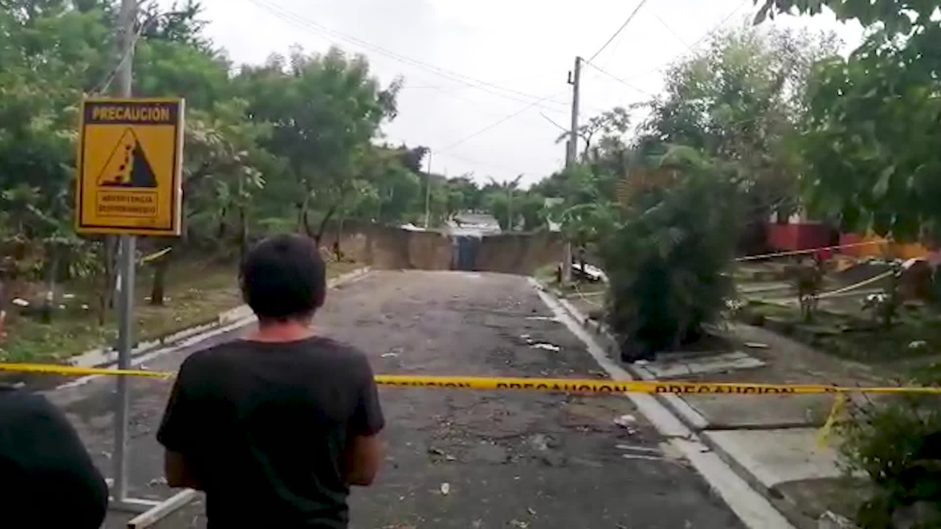 A sinkhole in a San Salvador suburb was made worse by heavy tropical moisture in the area.