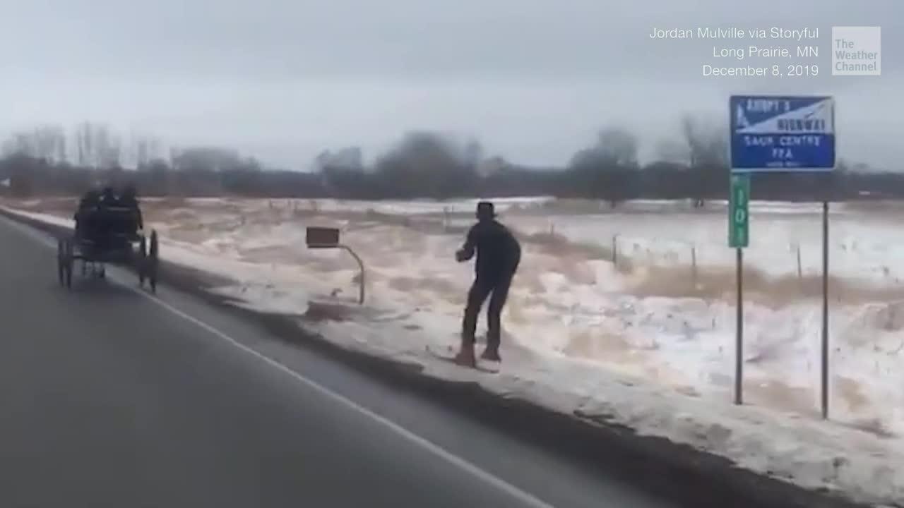 Un hombre esquía aprovecha el aventón de una carreta Amish en Minnesota.
