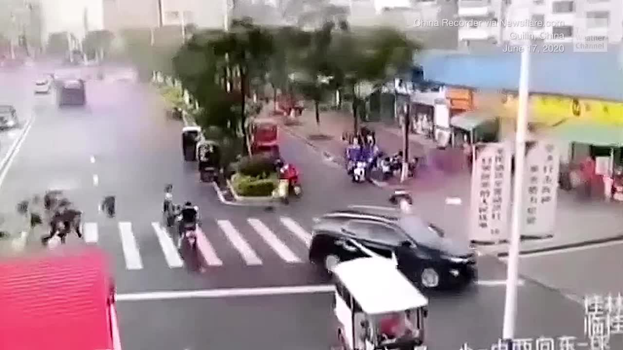 Cameras capture the dramatic moment strong winds in southern China rip off a canopy, sending it onto people and vehicles below.