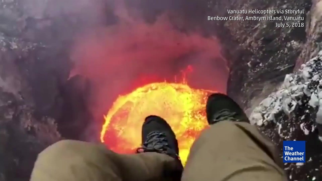 Helicopter pilot records himself dangling from zipwire above lava