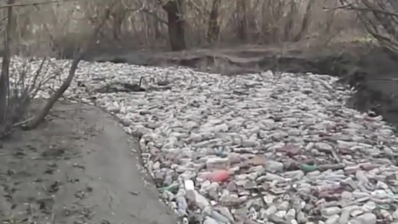 river in russia clogged by vast numbers of plastic bottles